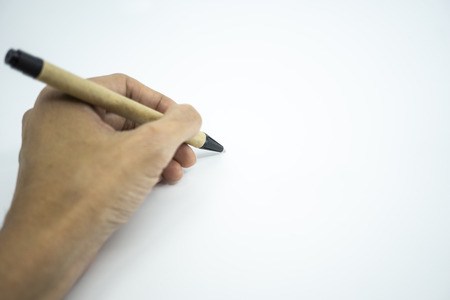 Hand holding ballpoint pen pointing on white paper. Selective focus.