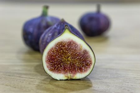 Fresh raw ripe figs on wooden background. Banco de Imagens