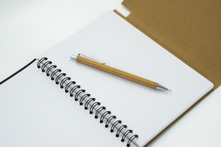 Mechanical pencil on white notebook isolated on white background. Selective focus.