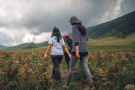 three girls walking through savana Stock Photo - 82174498