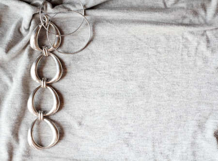 Silver bracelet and silver earrings on grey cotton Stock Photo