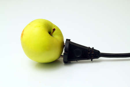 Green apple with electrical cord on white background