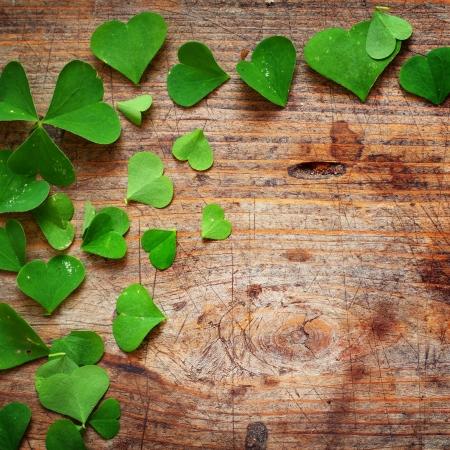 Green shamrock leaves on wooden background