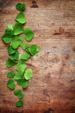 Green leaves with shape of heart on wooden background Stock Photo - 16776497