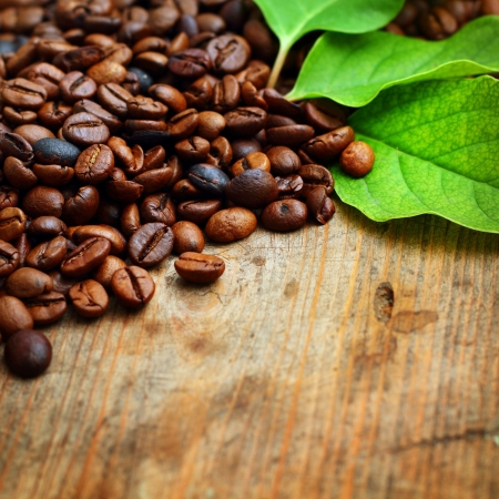 roasting: Coffee on wooden background with green leaves Stock Photo