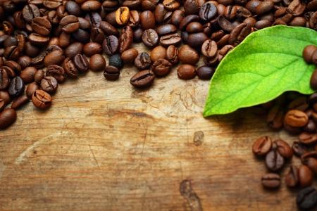 Café sobre fondo de madera con hojas verdes
