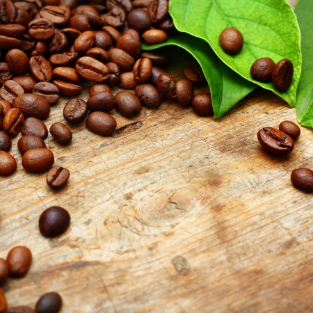 Coffee on wooden background with green leaves Stock Photo - 16776009