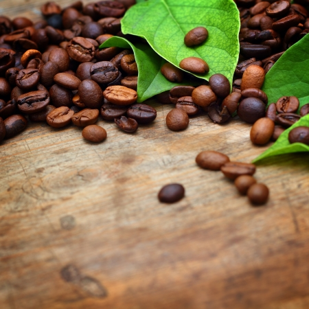 Coffee on wooden background with green leaves Stock Photo - 16775777