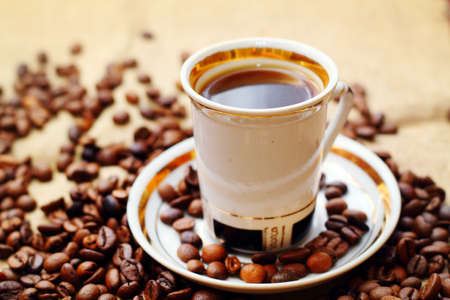 Coffee in white cup on burlap background