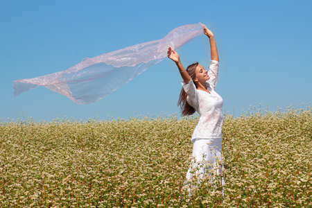 Young girl raising her hands with fabric on field with flowers Stock Photo - 18130531