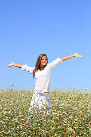 Happy woman in beauty field with white flowers photo