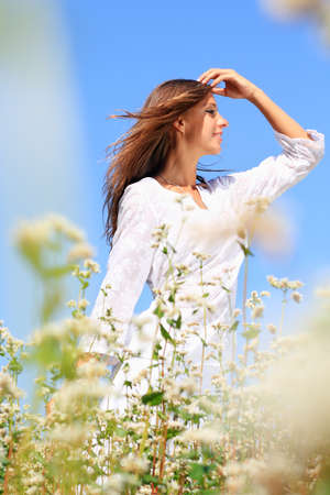 Happy woman in beauty field with white flowers Stock Photo