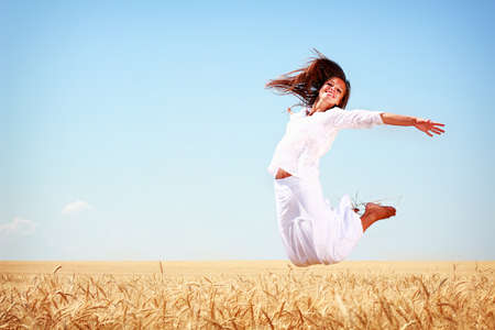 Happy young woman jumping in golden wheat field photo