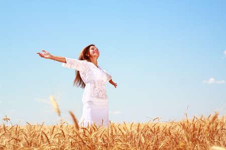 cosecha de trigo: Mujer joven feliz en campo de trigo dorado Foto de archivo