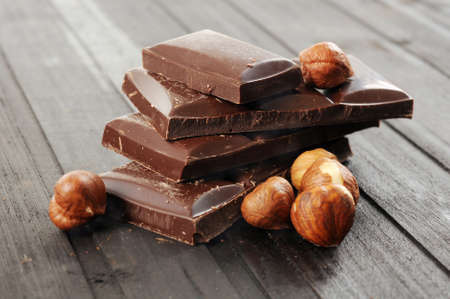 Chocolate and nuts on wooden background