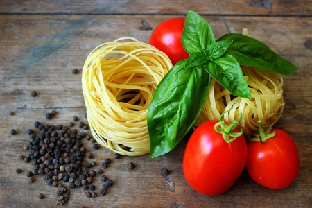 Raw tagliatelle with tomatoes on wooden background