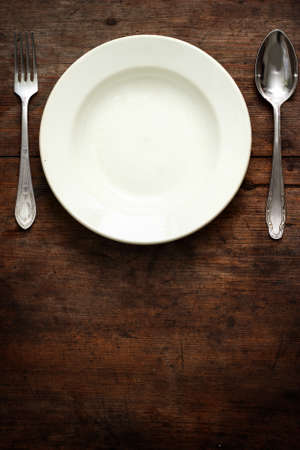 Empty plate with spoon and fork on wooden background Stock Photo