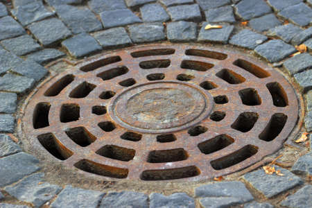 Old steel sewer manhole on the cobblestone road Stock Photo