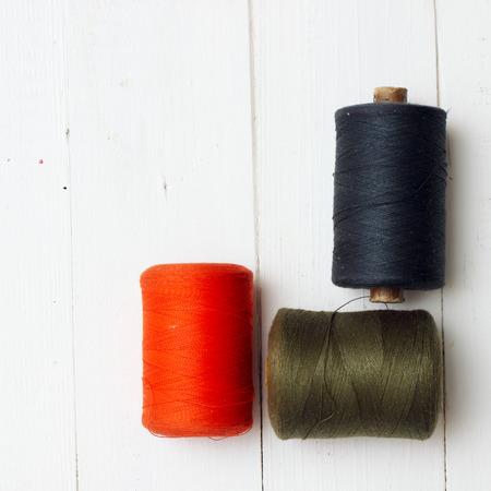Thread ravels on white wooden background Stock Photo