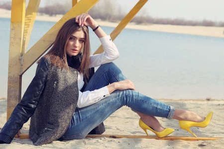 Young woman sitting on the sand Stock Photo