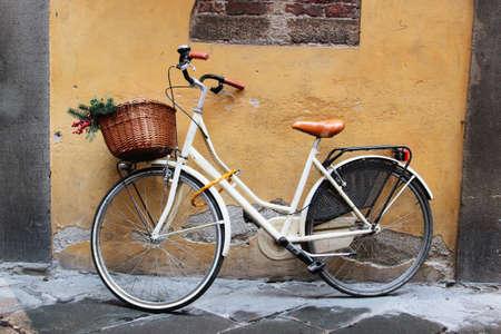 bicicleta: Blanca bicicleta retro con mimbre marrón de pie en la pared, Italia