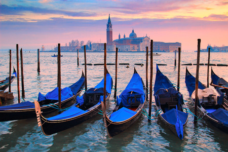 Picturesque view of blue gondolas in the night in Venice, Italy.