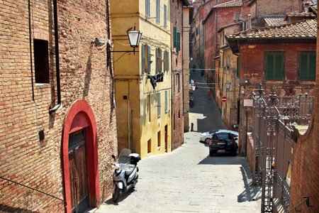 sienna: SIENA, ITALY - AUGUST 07, 2015: Old streets in Siena town, Italy. Aged buildings  at the street. Summertime. Editorial