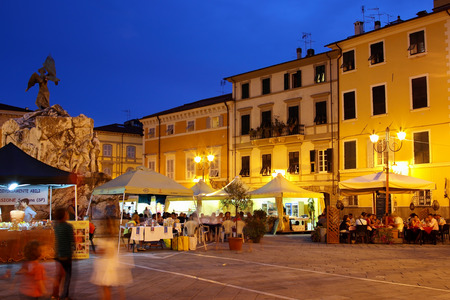 SARZANA, ITALY - AUGUST 10, 2015: People eating Italian food in the evening at the old  square - Piazza Giacomo Matteotti in old Sarzana, Italy. Editorial