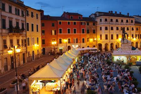 sarzana: SARZANA, ITALY - AUGUST 10, 2015: People tasting traditional Italian cuisine at the square - Piazza Giacomo Matteotti in Sarzana, Italy. View above night historical city.