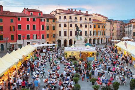 sarzana: SARZANA, ITALY - AUGUST 10, 2015: People tasting Italian cuisine at the old  square - Piazza Giacomo Matteotti in old Sarzana, Italy.