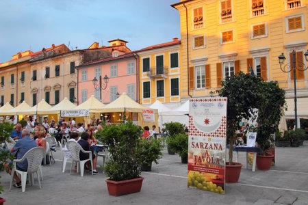 sarzana: SARZANA, ITALY - AUGUST 10, 2015: Local food festival at the historic square - Piazza Giacomo Matteotti in Sarzana town, Italy. People eating traditional Tuscany food.