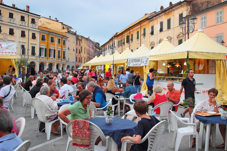 SARZANA, ITALY - AUGUST 10, 2015: Historic center square - Piazza Giacomo Matteotti, Sarzana city, Italy. People eating local food at summer fair that takes start every August. Editorial