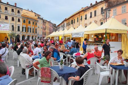 sarzana: SARZANA, ITALY - AUGUST 10, 2015: Historic center square - Piazza Giacomo Matteotti, Sarzana city, Italy. People eating local food at summer fair that takes start every August. Editorial