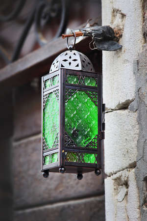 green been: Street lamp with bright green glass in the old city, Venice, Italy. Lamp has been made of black painted steel.