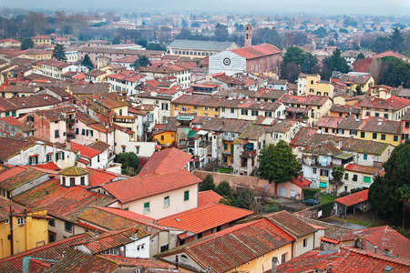 italian architecture: Historic aged medieval city of Lucca, Italy. View above the red old roofs of houses. Typical Italian architecture. Stock Photo