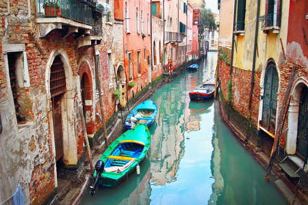 historic place: Winding narrow canal in Venice, Italy. Building facades are olded by weather and water. Historic place.