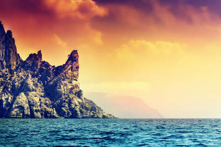 filtered: Sea and mountains at sunset. Filtered image. Stock Photo