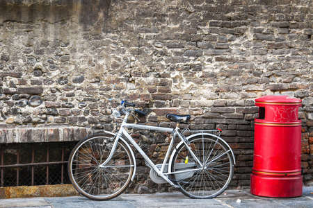 urn: Bicycle standing on the street near red urn, Italy.