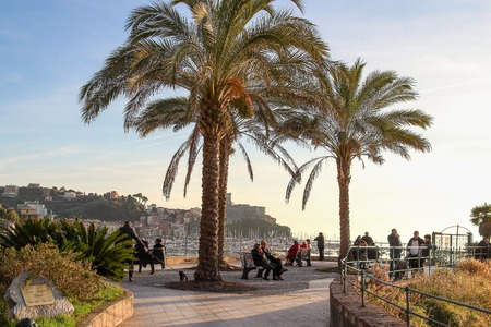 LERICI, ITALY - DECEMBER 25, 2015: People sitting under the palms and looking at the sea in Lerici, Italy.