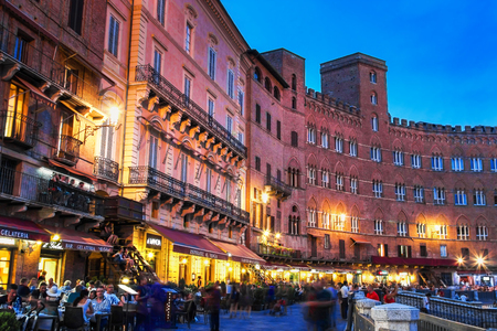 sienna: SIENA, ITALY - AUGUST 07, 2015: Old Piazza del Campo in the night in Siena, Tuscany region, Italy. Many tourists are eating at open restaurants. Editorial
