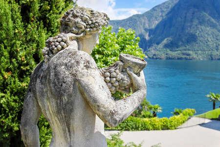 VILLA BALBIANELLO, ITALY - AUGUST 02, 2015: Old statue of man with vine in the park, villa Balbianello, Como lake, Italy.
