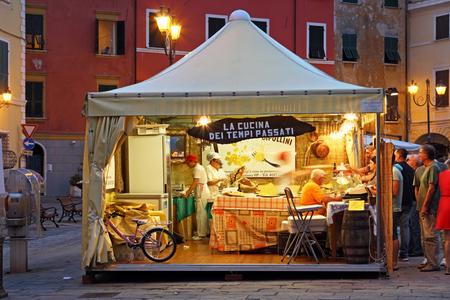 sarzana: SARZANA, ITALY - AUGUST 10, 2015: View inside the open tent on the square - Piazza Giacomo Matteotti in Sarzana, Italy. Summer local food festival.