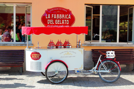 COMO LAKE, ITALY - AUGUST 02, 2015: Street sale of home made ice cream in Lenno, Como lake, Italy. Bicycle cart with red tent.