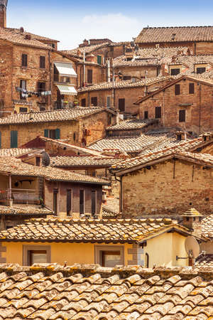 View of many tile roofs of old houses in Siena, Tuscany, Italy.