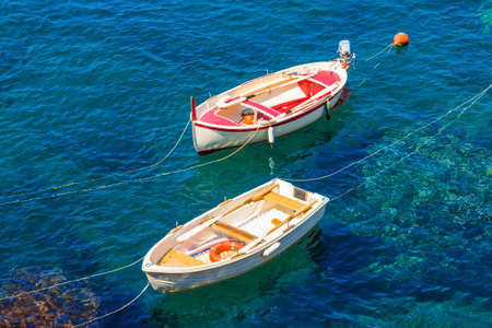 Two colorful boats on the sea. Transparent blue water in summer. Cinque Terre, Italy. Stock Photo