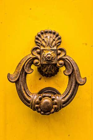 Old metal door knob on yellow background.