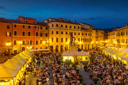 SARZANA, ITALY - AUGUST 10, 2015: People tasting traditional Italian food in the evening at the square - Piazza Giacomo Matteotti in Sarzana, Italy. Editorial