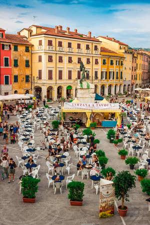 SARZANA, ITALY - AUGUST 10, 2015: People tasting Italian cuisine at the old  square - Piazza Giacomo Matteotti in old Sarzana, Italy.