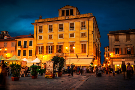 SARZANA, ITALY - AUGUST 10, 2015: People eating traditional Italian cuisine on the square - Piazza Giacomo Matteotti in Sarzana, Italy. Summer food festival.