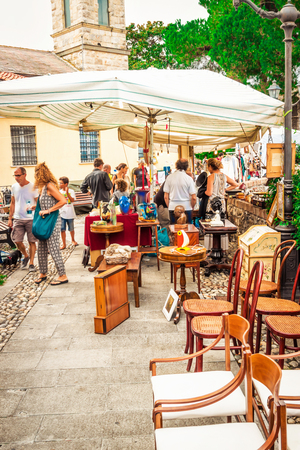SARZANA, ITALY - AUGUST 10, 2015: People walking at the market of old home vintage objects and furniture in small town of Sarzana, Liguria, Italy.